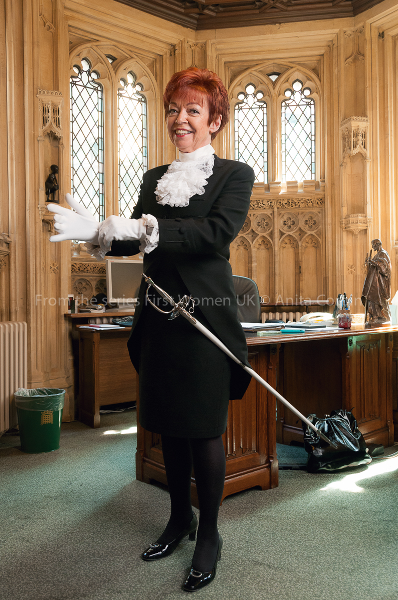 A woman wearing a black skirt and blazer putting on a pair of white gloves. A sword is hanging from her left hip. She is standing in front of a desk and ornate windows.