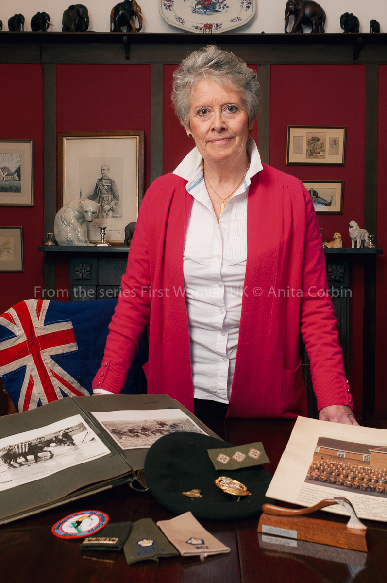 A woman wearing a white shirt and red cardigan standing behind a desk with military paraphernalia.