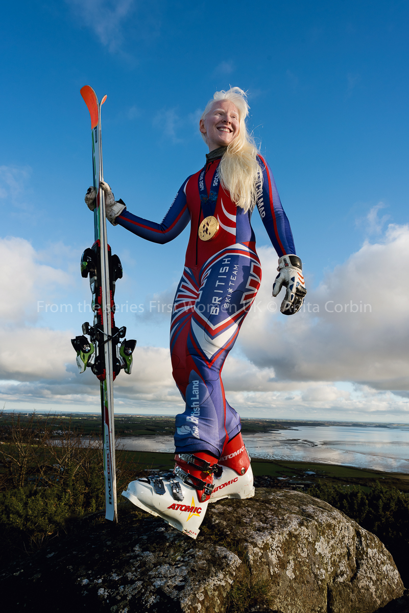 A woman standing on a large rock wearing ski clothing and holding skis in her right hand.