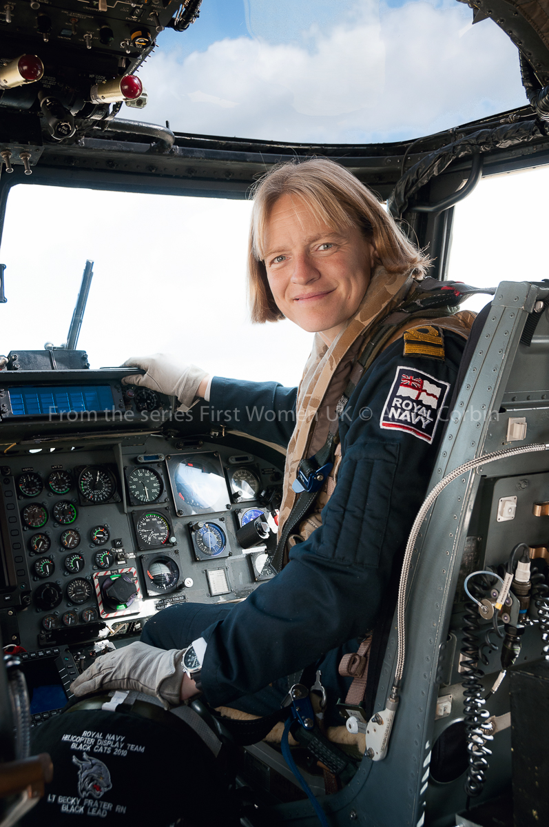 A woman with a Royal Navy patch on her sleeve sitting in the cockpit of a helicopter.