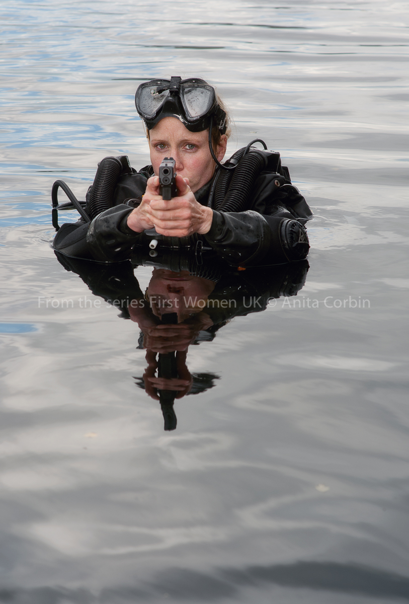 A woman standing in open water with her head and shoulders above water. She is wearing black diving gear and pointing a gun in the direction of the camera.