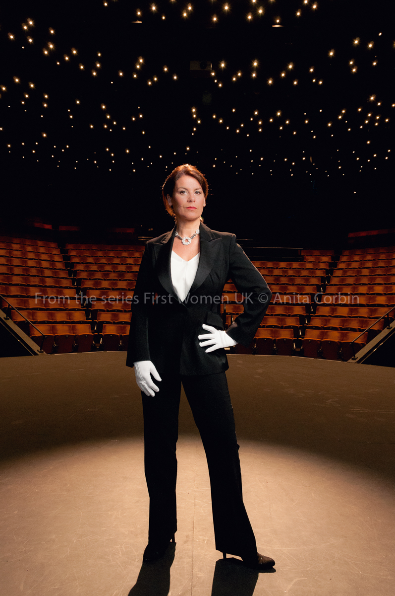 Woman wearing a black suit standing on a stage with a spotlight on her.