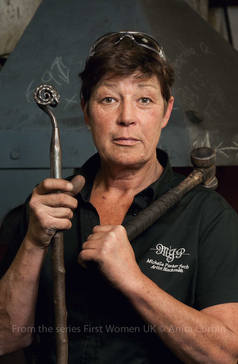 A woman wearing a black shirt holding blacksmith tools in her hands including a hammer over her shoulder.