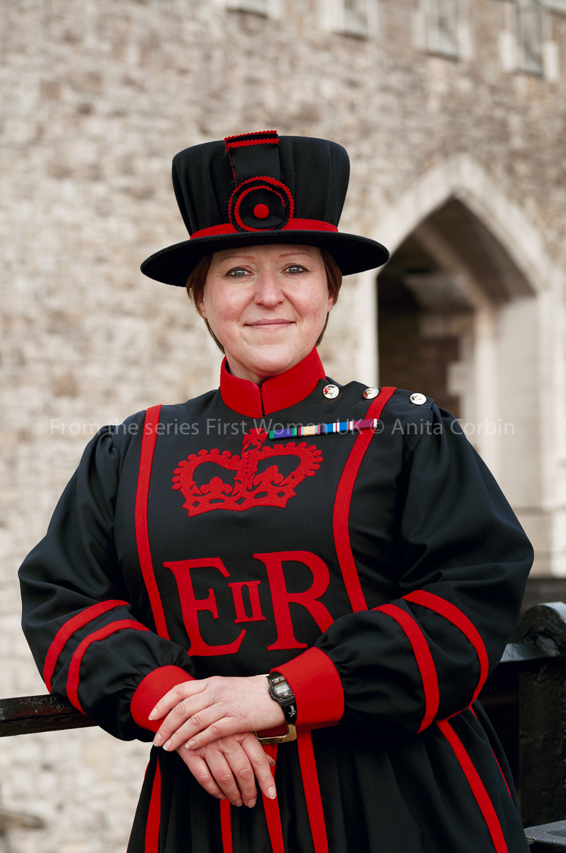 A woman dressed in yeoman warder uniform. The uniform is dark blue with red trimmings, including a crown and the letters EIIR. She is wearing a matching hat and medal ribbons are pinned on her uniform.