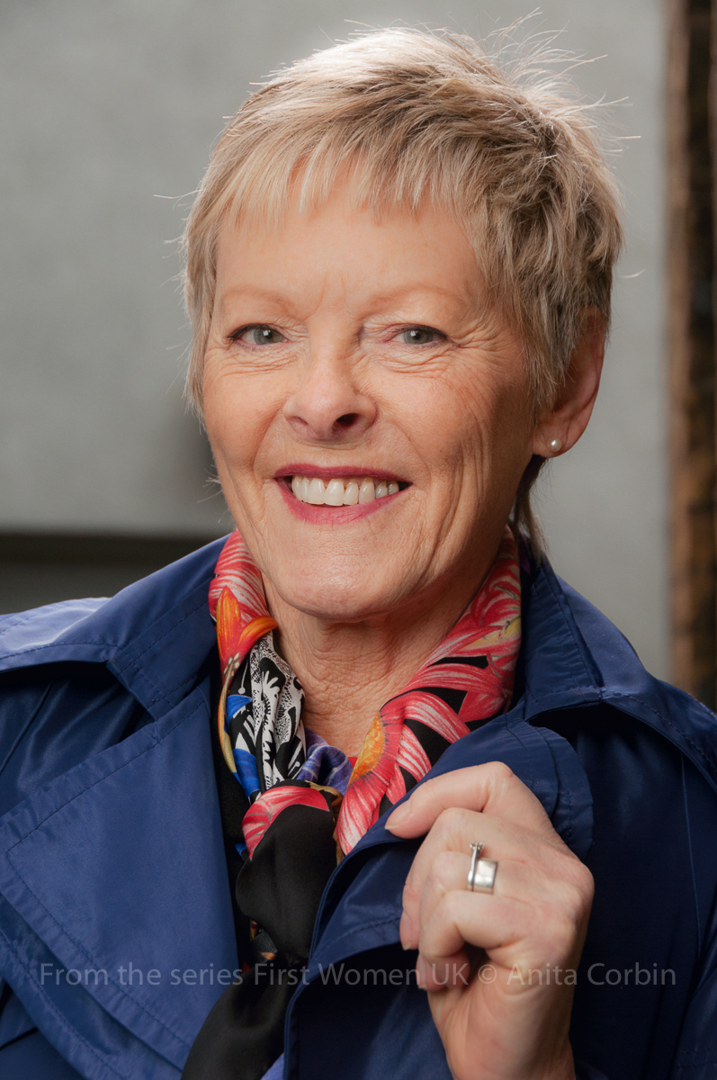 A woman wearing a blue collared jacket and a multicoloured scarf smiling at the camera.