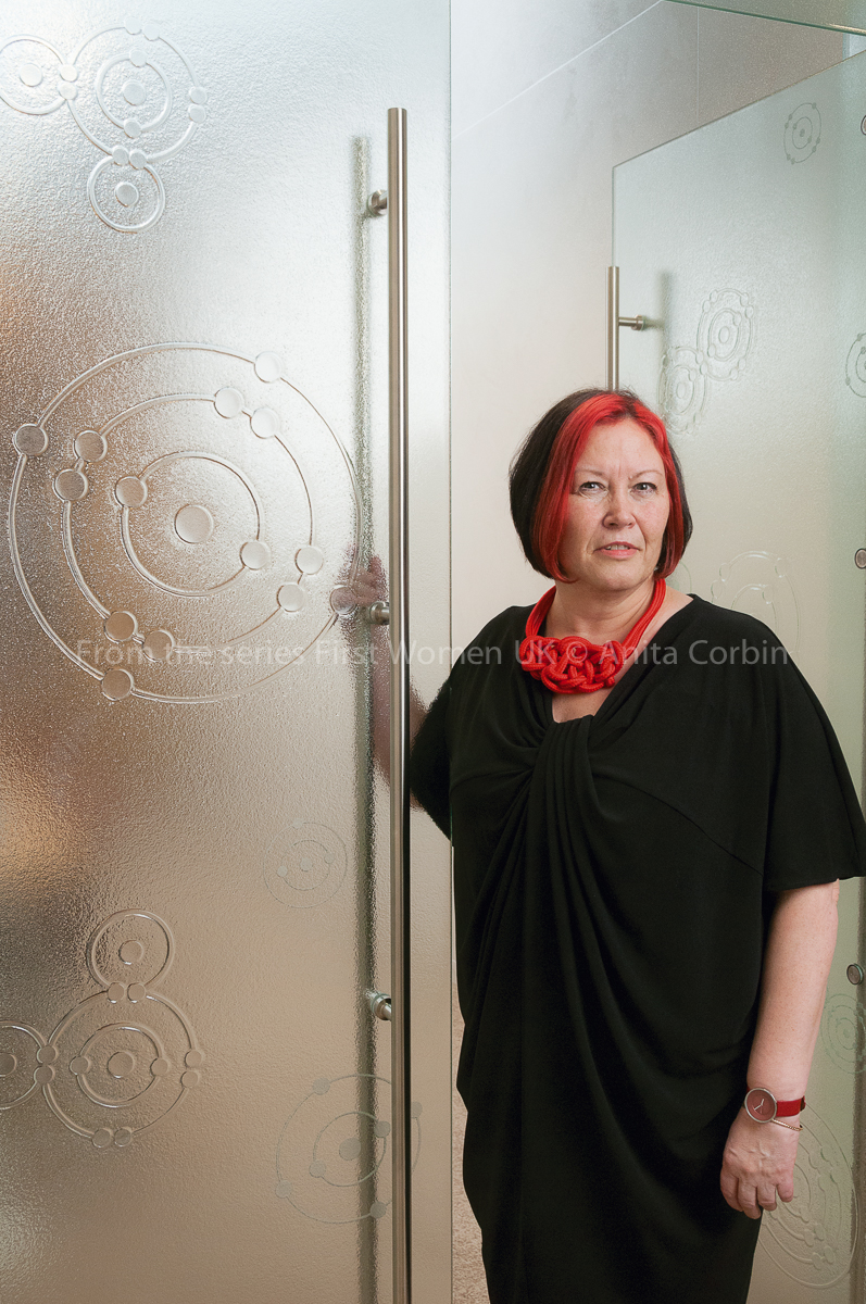 Woman standing in the doorway of frosted glass doors with a hand on one handle.