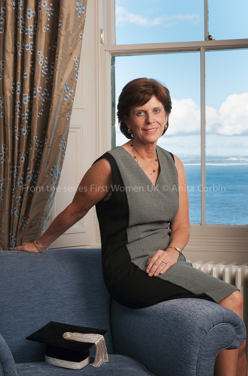 A woman sitting on the arm of an armchair wearing a black and grey dress. A mortar board is on the seat of the arm chair and a window overlooking the sea is behind her.