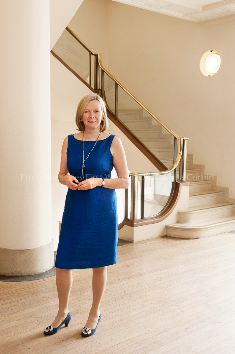 A woman in a blue dress standing in a light room with a staircase behind her.
