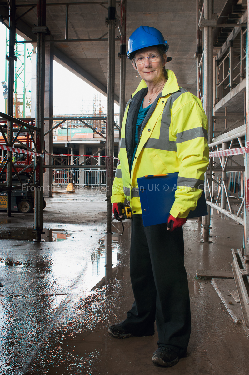 A woman in a hi-vis jacket and blue hard hat with a blue clipboard in her left hand standing in a construction site.