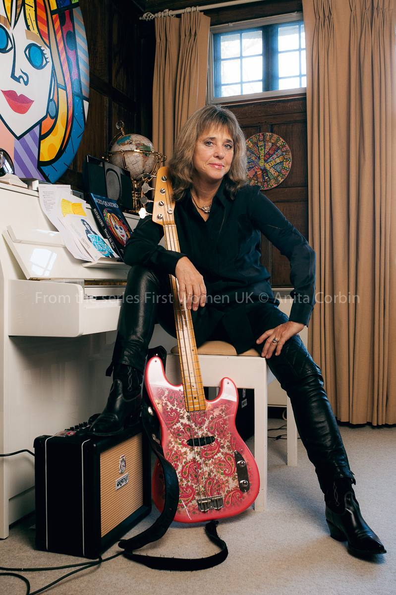 Woman dressed in black sitting on a piano stool with one leg on an amplifier and an electric guitar in her hand. She is sitting with her back to a white piano with miscellaneous objects on top, including a globe.