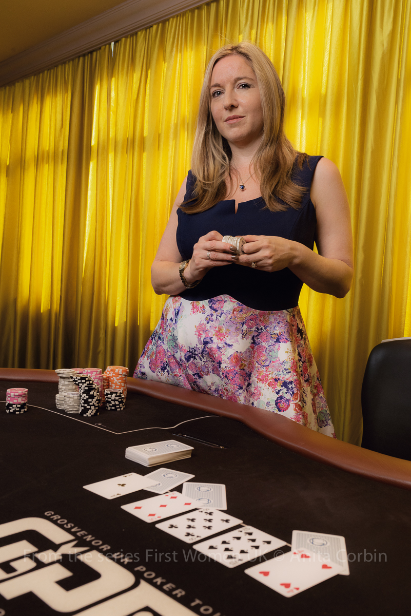 A woman standing behind a poker table in front of a yellow curtain with poker chips in her hand.